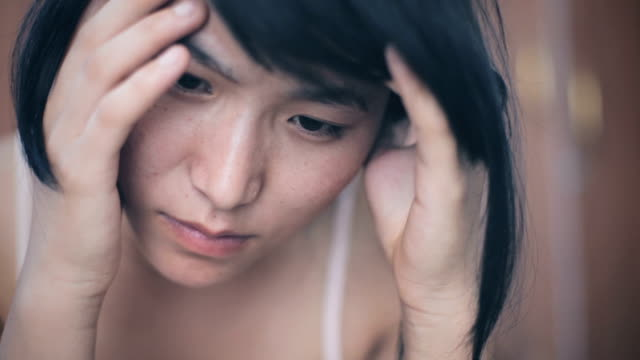 asian young woman holding head and feeling headache. - emotional stress stock videos & royalty-free footage