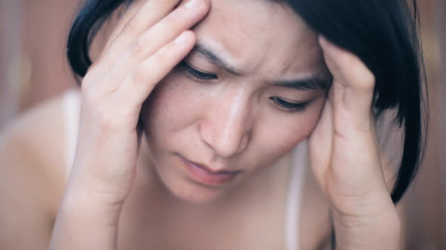 asian young woman holding head and feeling headache. - stanco video stock e b–roll