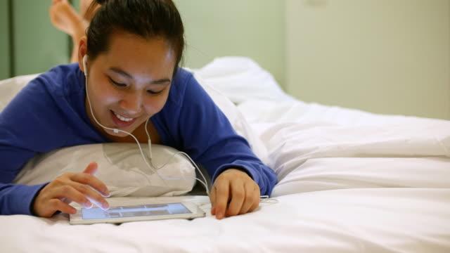 アジア若い女性のベッドでお気に入りの音楽を聞きながら、4 k (uhd) - サウンドトラック点の映像素材/bロール