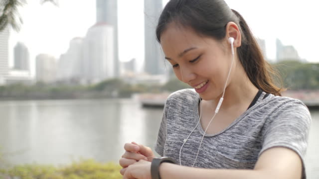 asian young woman monitoring her running performance on smartwatch - interval start stock videos & royalty-free footage