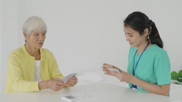asiatische junge frau krankenschwester oder haus gesundheit helfer spielen karten mit senior-paar am tisch im wohnzimmer zu hause für häusliche gesundheitsversorgung konzept. - hausbesuch stock-videos und b-roll-filmmaterial