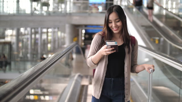 asian young woman on smart phone at airport - asian stock videos & royalty-free footage