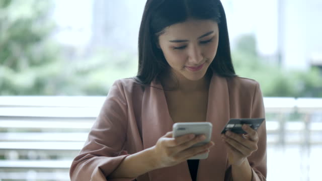 asian young woman online shopping - applicazione mobile video stock e b–roll