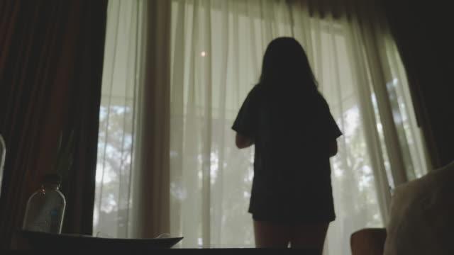 アジアの若い女性は、リゾートのバルコニーの外の景色を見るために朝にカーテンを開きます - 窓越し点の映像素材/bロール