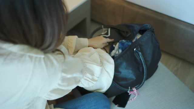 asian young woman packing suitcase . - struggle stock videos & royalty-free footage