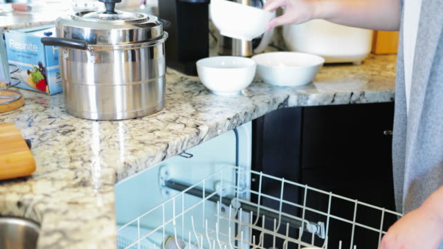 asian young woman put dirty stuff in dishwasher - dishwasher stock videos & royalty-free footage