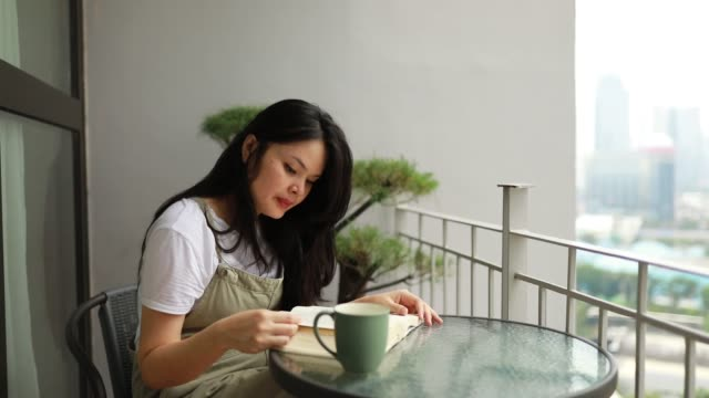 asian young woman reading book on balcony - indonesia stock videos & royalty-free footage