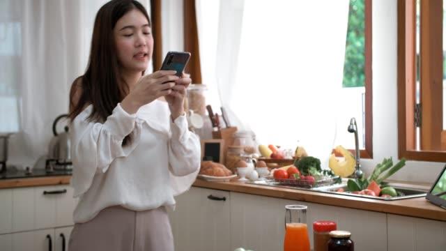 vidéos et rushes de jeune femme asiatique enregistrant la vidéo pour préparer la nourriture à la maison - influenceur