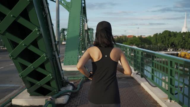 都市橋の上を走るアジアの若い女性 - 女子トラック競技点の映像素材/bロール