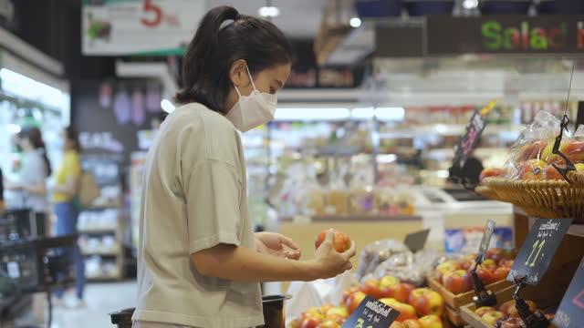 vídeos de stock, filmes e b-roll de mulher jovem asiática fazendo compras em supermercado - espontânea