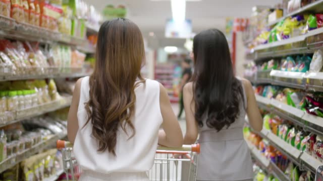 asian young woman shopping in supermarket, slow motion. - snack stock videos & royalty-free footage