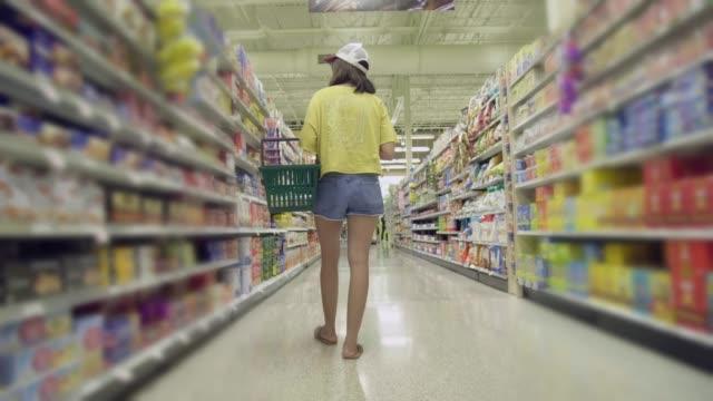 アジアの若い女性がスーパー マーケットでのショッピング - おやつ点の映像素材/bロール