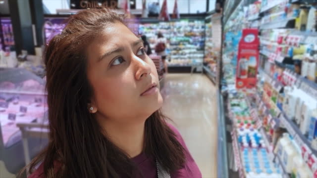 asian young woman shopping in supermarket - decisions stock videos & royalty-free footage