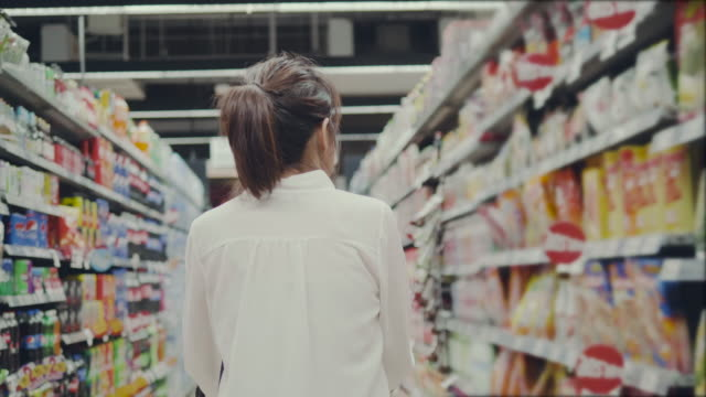 vídeos de stock e filmes b-roll de asian young woman shopping in supermarket - prateleira objeto manufaturado