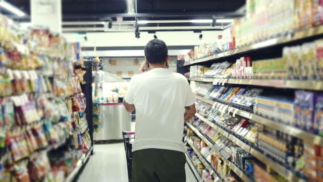 vídeos y material grabado en eventos de stock de asiática joven comprando con carrito de compras en supermercado - hípster urbano
