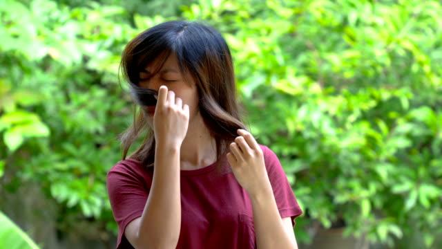vídeos y material grabado en eventos de stock de mujer asiática joven huele su pelo - malos olores