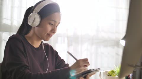 stockvideo's en b-roll-footage met aziatische jonge vrouw studeren online thuis - study