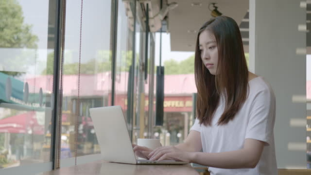 Asian young woman talking on the phone in a cafe and looking at the screen of her laptop during her coffee break
