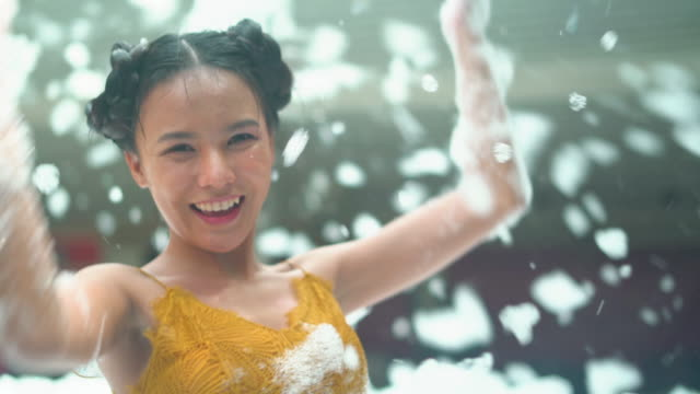 asian young woman throwing the soap sun toward camera - soap sud video stock e b–roll