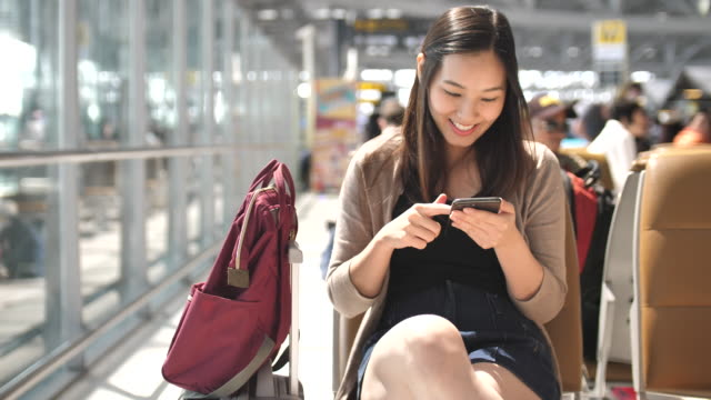 vídeos de stock e filmes b-roll de asian young woman touching on smart phone while waiting for her flight, slow motion - bilhete
