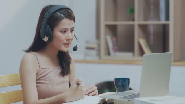 vidéos et rushes de jeune femme asiatique utilisant le casque regardant l'écoute d'ordinateur portatif et apprenant des cours en ligne - centre d'appel
