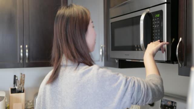 電子レンジを使用してアジアの若い女性 - 電子レンジ点の映像素材/bロール