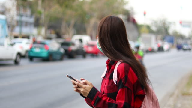 asian young woman using smart phone in the city - corona stock videos & royalty-free footage