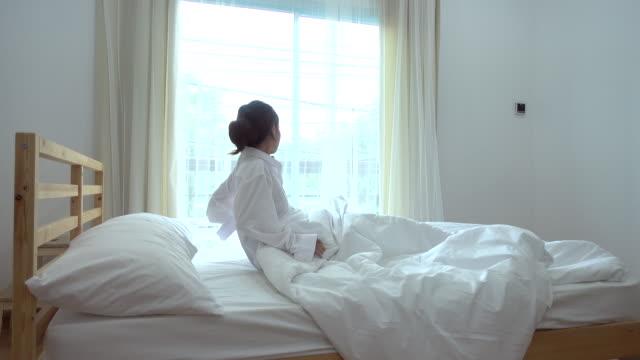 アジアの若い女性の寝室に目覚める - 寝室点の映像素材/bロール