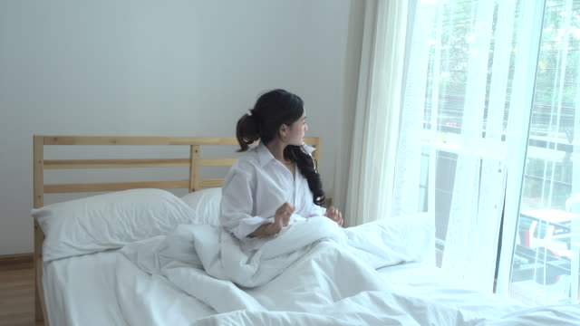 Asian Young Woman waking up on the bedroom