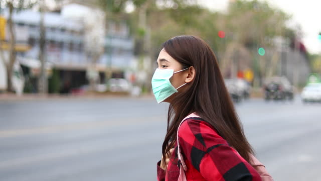 vídeos de stock e filmes b-roll de asian young woman walking in the city wearing face mask because of air pollution, particulates and for protection flu virus, influenza, coronavirus - estilo de vida pouco saudável