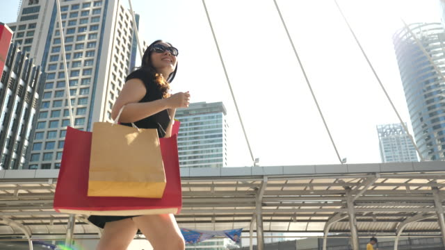 asian young woman walking with shopping bags - shopping bag stock videos & royalty-free footage
