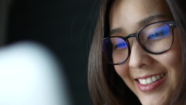 asian young woman watching information of computer screen, reflection in glasses - home shopping stock videos & royalty-free footage