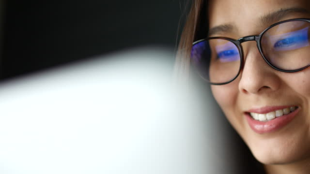 asian young woman watching information of computer screen, reflection in glasses - advice stock videos & royalty-free footage