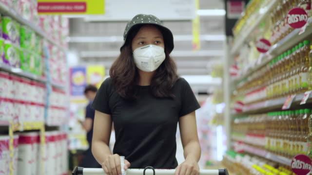 スーパーマーケットのストックビデオで買い物をする保護フェイスマスクを身に着けているアジアの若い女性 - 選択点の映像素材/bロール