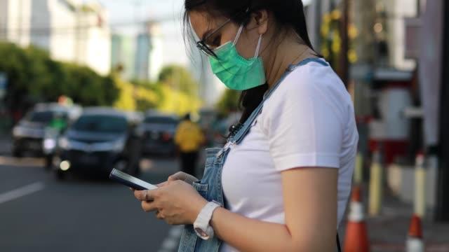 vídeos y material grabado en eventos de stock de asiática joven que lleva máscara esperando taxi en la calle - yakarta