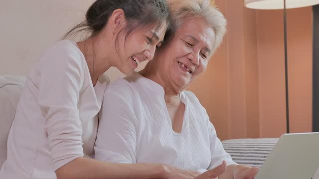 vidéos et rushes de jeune femme asiatique avec la grand-mère âgée de 64 ans utilisant des achats en ligne sur l'ordinateur de labtop à la maison pendant la distanciation sociale pour empêcher des épidémies de coronavirus ou de concept de magasinage covid-19.online. - new age concept