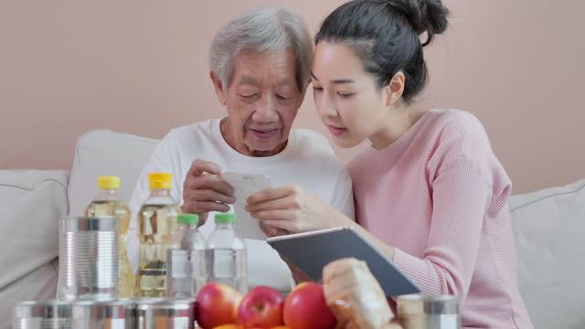 vidéos et rushes de jeune femme asiatique avec l'âge de grand-mère 80 ans utilisant des achats en ligne sur l'ordinateur de tablette à la maison pendant la distanciation sociale pour empêcher des épidémies du coronavirus ou du concept covid-19.online shopping. - new age concept