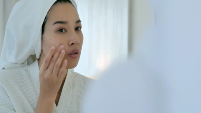 asian young woman's cheek with typical problem with acne and pimples in the adulthood time.young women with problem skin in bathroom.skin problem,acne,skin care concept - mirror stock videos & royalty-free footage