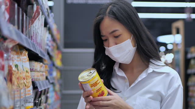 asian young women age 25 yearold in protective medical mask buys basic necessities at supermarket during covid-19 coronavirus epidemic.grocery shopping concept. - label stock videos & royalty-free footage
