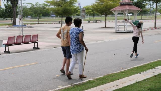 asiater äldre kvinna som går i parken med sina barnbarn tillsammans, livsstilskoncept. - gå tillsammans bildbanksvideor och videomaterial från bakom kulisserna