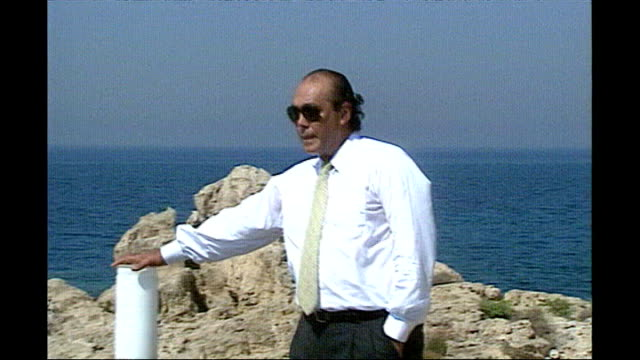 asil nadir convicted of theft lib guzelyurt asil nadir walking along clifftop and looking out to sea - at the edge of stock videos and b-roll footage