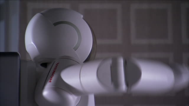 asimo, a humanoid robot, raises its arm and twists its head. - asimo stock videos & royalty-free footage