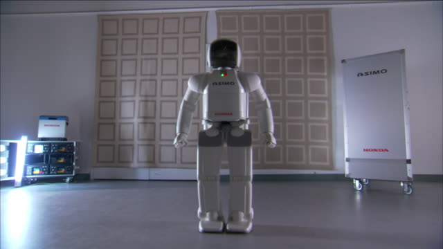 asimo, a humanoid robot,  raises its arms above its head. - asimo stock videos & royalty-free footage