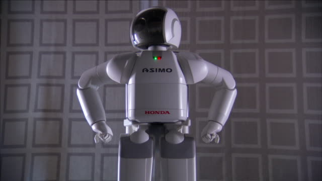 asimo, a humanoid robot, raises its arms to its hips and twists its head. - asimo stock videos & royalty-free footage