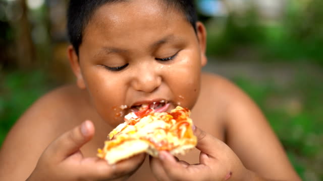 asisn boy eat pizza outdoor - overweight child stock videos & royalty-free footage