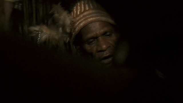 Asmat tribesmen from the village of Yaosakor play drums, dance and recite poetry late into the night, Papua.