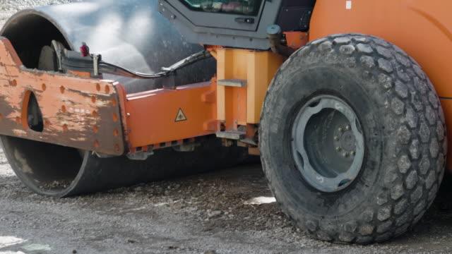 stockvideo's en b-roll-footage met cu. asfaltroller werken. wegenbouw. transportsector. groeiende steden. - boven water komen