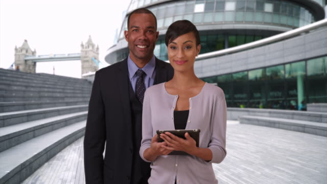 aspiring black male and female business partners standing outside in london - medarbetarengagemang bildbanksvideor och videomaterial från bakom kulisserna