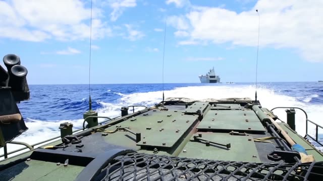 Assault amphibious vehicles assigned to Combat Assault Company 3rd Marine Regiment pick troops up from shore at Poholokoa Training Area during the...