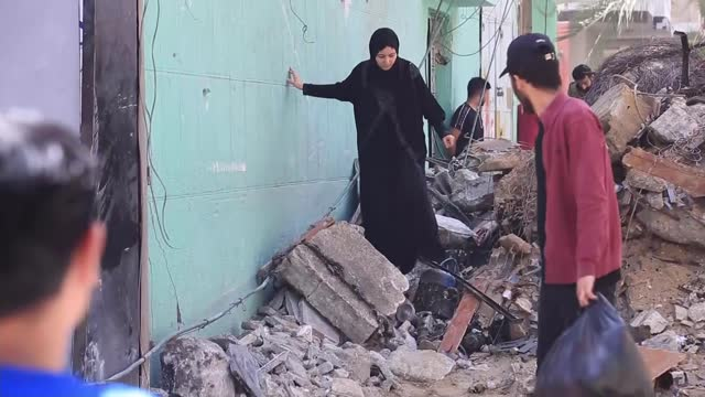 assault on gaza continues as tensions rise within the country; palestine: gaza: ext tracking nadin abd al-latif along street past rubble of destroyed... - striscia di gaza video stock e b–roll
